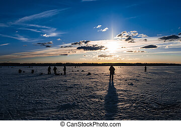 silhouettes of fishermen fishing and ice screws in winter on the lake