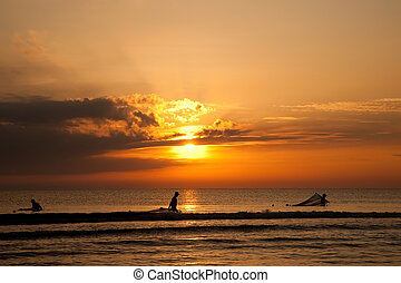 Silhouettes Of Fishermen In The Sea