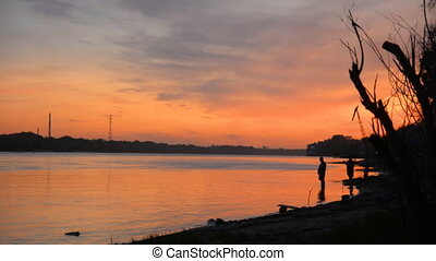 Silhouettes of fishermen on the river bank,