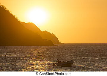 Silhouettes of fishers in Taganga bay with sunset