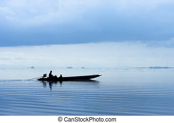 Silhouettes of fishing boat on the lake in blue hour