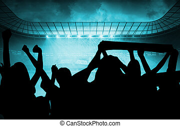 Silhouettes of football supporters against misty football...