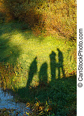 Silhouettes of four tourists on the background of green nature