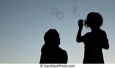 girl blowing up soap bubbles and boy catching them -...