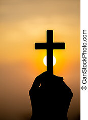 Silhouettes of girl hands praying to the GOD while holding a crucifix symbol with bright sunbeam on sunrise background