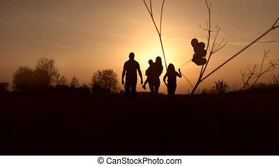 Silhouettes of happy family watching sunset