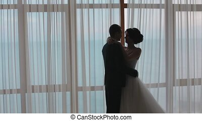 Silhouettes of honeymooners standing next to the window