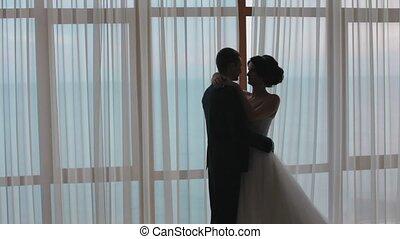 Silhouettes of honeymooners standing next to the window