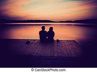 Silhouettes of hugging couple against the sunset sky