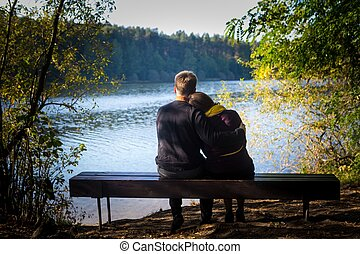 Silhouettes of hugging couple sitting on bench against the lake at sunset