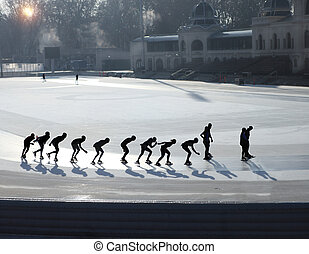 Silhouettes of ice skating people on ice