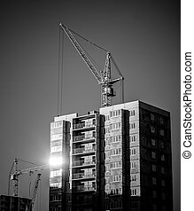 silhouettes of industrial construction cranes and building