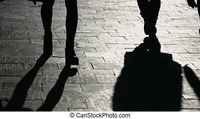 Silhouettes of legs of walking people crossing shadows