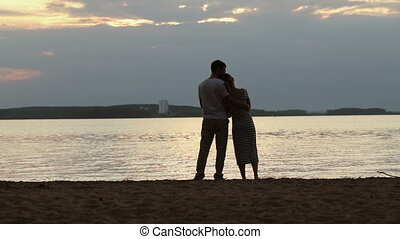 Silhouettes of lovers at sunset. Young beautiful couple embracing on a shore of the lake