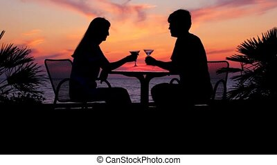 silhouettes of man and woman drinking wine sits at table against sunset sky