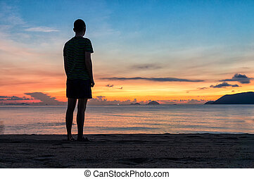 Silhouettes of man on beach at a colorful sunrise with amazing sky over ocean