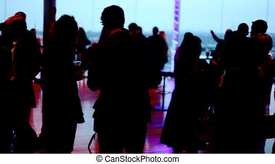 Silhouettes of many people who relax in some bar