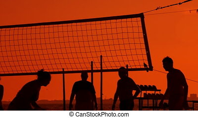 Silhouettes of men and women playing beach volleyball