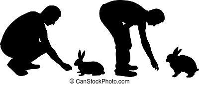 Silhouettes of men feeding rabbits