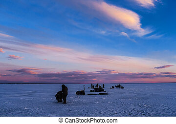 silhouettes of men fishermen and snowmobiles on winter fishing