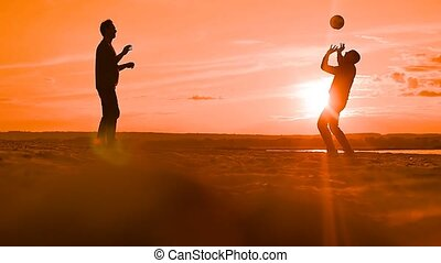 Silhouettes of men playing volleyball slow motion video - at...