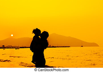 silhouettes of mother and baby kissing on sunset