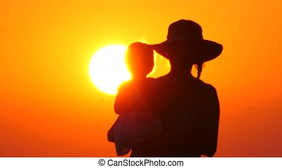 Silhouettes of mother and child in her arms on the ...