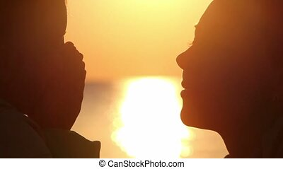 Silhouettes of mother and daughter heads, girl close face by palms