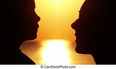 Silhouettes of mother and daughter heads, then daughter hugging mother