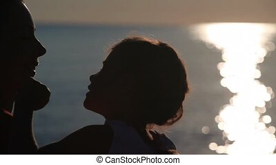Silhouettes of mother and daughter heads, they are talking and girl puts arm on mother shoulder