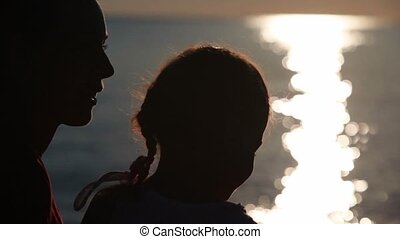 Silhouettes of mother and daughter heads with sunshine reflected in water behind
