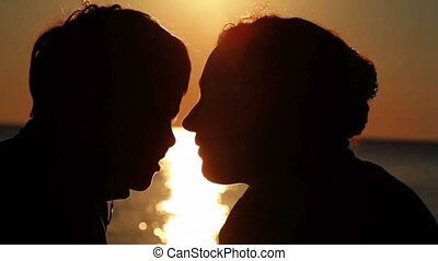 Silhouettes of mother and her son heads very close