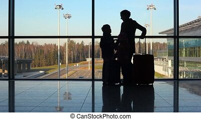 silhouettes of mother, son and daughter standing against window