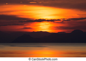 Silhouettes of mountain with sunset at the lake, Thailand.