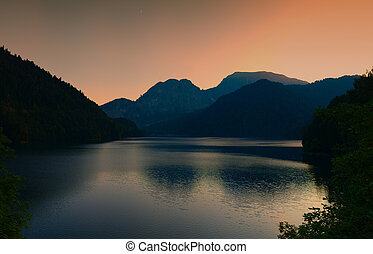 Silhouettes of mountains at sunset on a mountain lake