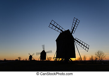 Silhouettes of old windmills by sunset - Silhouettes of old...