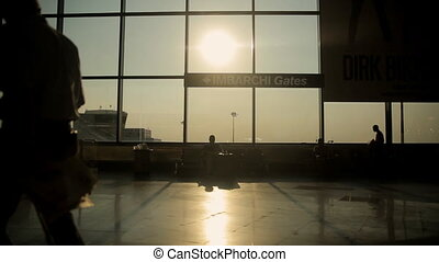 Silhouettes of passengers in the airport lounge at sunset
