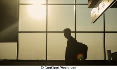 Silhouettes of passengers in waiting room of the airport