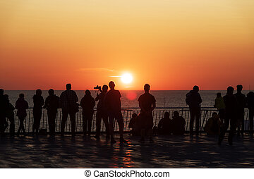 Silhouettes of people against the setting sun on deck of a cruise ship