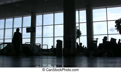 Silhouettes of people against windows in an airport hall