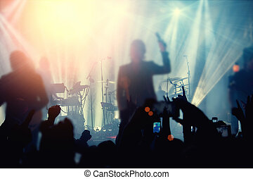 Silhouettes of people and musicians in big concert stage