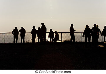 Silhouettes of people at the fence over a cliff