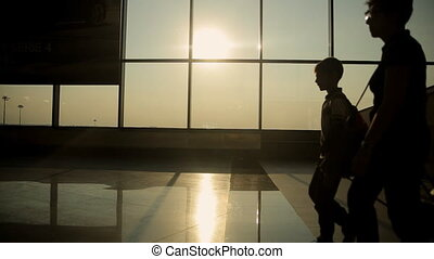 Silhouettes of people coming for a landing on the flight in Milan airport