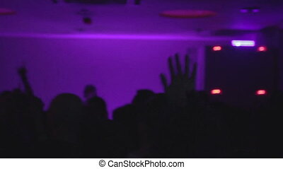 """Silhouettes of people dancing, waving hands at nightclub party"""