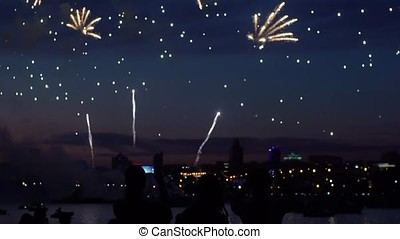 Silhouettes of people during fireworks in the background of a night city