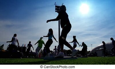Silhouettes of people engaged in step aerobic exercise on stadium at sunny autumn day