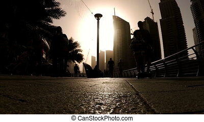 Silhouettes of people engaged in walking and Jogging in Dubai Marina at sunset