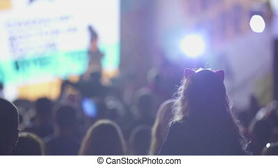 silhouettes of people in a crowd on the background of the stage at a concert