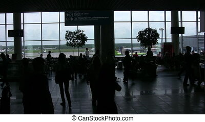 Silhouettes of people in a hall of the airport