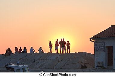 Silhouettes of people on a sunset background